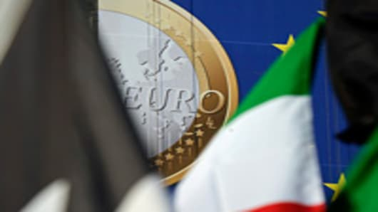 The Italian national flag, is seen against a giant euro banner featuring an image of a euro coin.