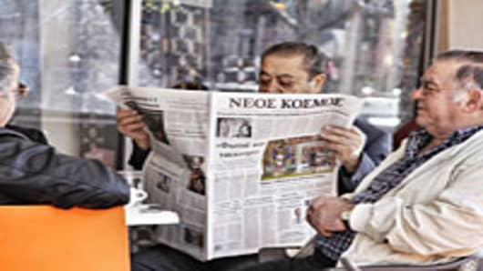 A man reads a Greek-language newspaper at a cafe in Oakleigh, a suburb of Melbourne, Australia.