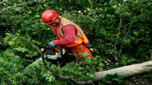 Crews clear a fallen tree from the sidewalk along New York Avenue NW on June 30, 2012 in Washington. The Washington area was hit by severe thunderstorm Friday night knocking trees down and left more then 400,000 without power during a record setting heatwave.