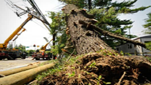 A partially uprooted tree is seen as Pepco employees work on damaged utility poles and lines along Bradley Blvd. near River Rd. on Sunday June 01, 2012 in Montgomery County, MD. Friday's powerful storm left scores without power.
