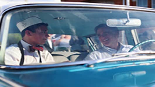 Republican presidential candidate, former Massachusetts Governor Mitt Romney sits in a 1961 Rambler with the cars owner, Michael Scheib, during a campaign event at K's Hamburger on June 17, 2012 in Troy, Ohio.