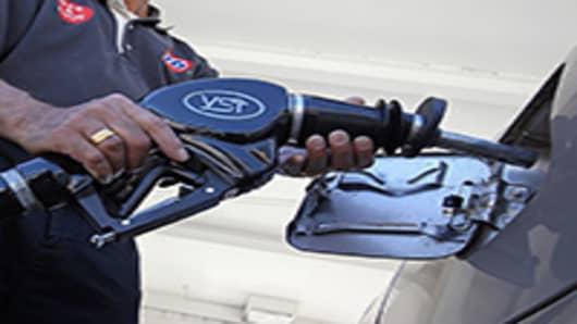 A worker pumps gasoline into a car.