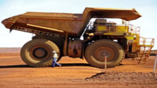 A driver inspects an earth mover at Fortescue Metals Group Ltd.'s Cloudbreak iron ore operation in the Pilbara region of Western Australia.