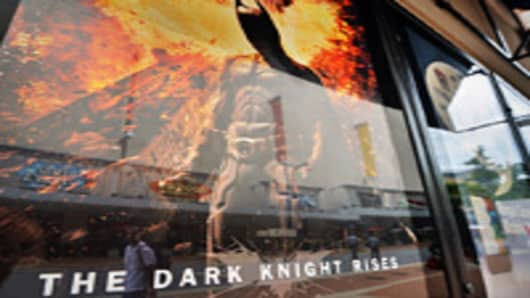People walk past a poster of the new Batman movie 'The Dark Knight Rises' outside a theater in Silver Spring, Maryland, on July 20, 2012. A masked attacker gunned down dozens of US moviegoers at the packed premiere of a Batman movie on Friday, killing at least 12 people and wounding 58.