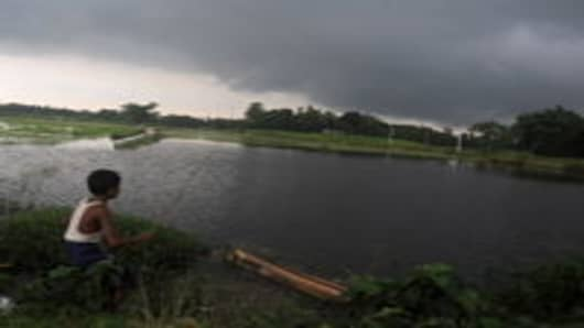 Indian children fish underneath monsoon clouds on the outskirts of Siliguri
