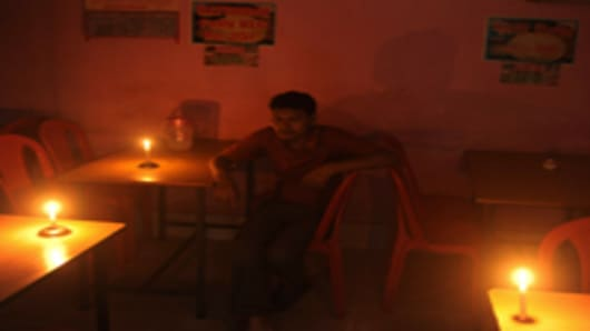 An Indian diner waits for his meal in candle light at a hotel during a power cut in Siliguri on July 31, 2012. A massive power failure hit India for the second day running as three regional power grids collapsed, blacking out more than half the country in a crisis affecting over 600 million people.