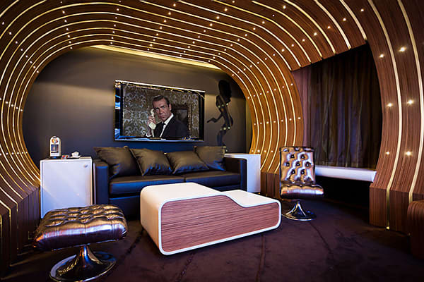 """Location: Hotel Le Seven, Paris, France Cost: From $550 per night James Bond fans will be both shaken and stirred by this homage to the sly spy. The den-like, retro retreat features its own Turkish bath, a complete library of Bond films, and, of course, some ultra-cool gadgets, including a TV screen that diffuses four different """"mood fragrances"""" and a lamp with a base made of a (fake) golden gun. Femme fatale not included."""