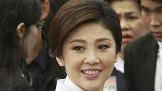 In this photo taken Aug. 10, 2011, Thai Prime Minister Yingluck Shinawatra smiles after a group photo with her cabinet members following an oath taking ceremony at the government house in Bangkok, Thailand.