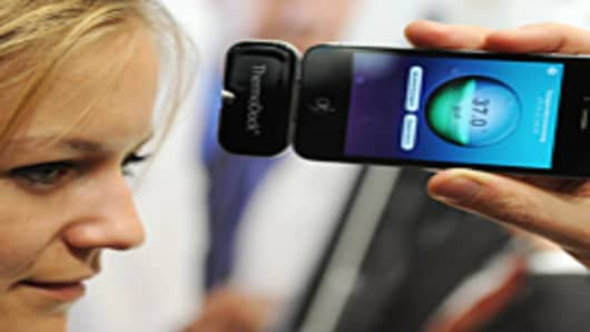 A woman tests an Iphone device for measuring body temperature at the 'Medica World Forum for Medicine' (MEDICA) fair on November 17, 2011 in Duesseldorf, western Germany.