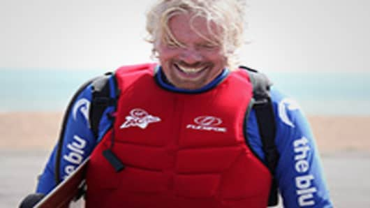 Sir Richard Branson arrives on the beach after attempting to cross the English channel by kite surfing.