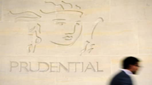 A pedestrian passes the Prudential Plc company logo, on display outside the company's headquarters in London, U.K., on Wednesday, Aug. 3, 2011.