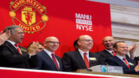 In this handout photo provided by the NYSE Euronext, Manchester United Executives Joel Glazer (2nd L) and Avram Glazer (C) prepare to ring the Opening Bell at the New York Stock Exchange on August 10, 2012 in New York City.