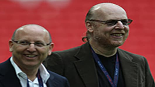 Manchester United's owners Malcom Glazer (L) and Steven Glazer attend their club's training session.