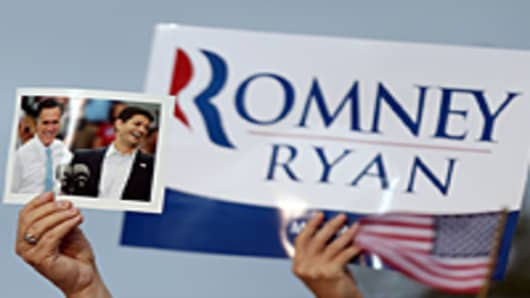 A supporter holds a photo Republican presidential candidate and former Massachusetts Governor Mitt Romney (L) and his running mate Rep. Paul Ryan (R-WI) during a campaign rally at the Waukesha County Expo Center on August 12, 2012 in Waukesha, Wisconsin.