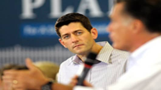 Republican vice presidential candidate, U.S. Rep. Paul Ryan (R-WI) listens to Republican presidential candidate, former Massachusetts Gov. Mitt Romney (R), talk to the crowd at the Absolute Style furniture factory on August 12, 2012 in High Point, North Carolina.