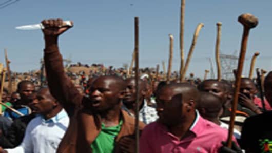 Striking mine workers demonstrate as they protest over wage demands outside the Nkageng informal settlement on August 16, 2012 in North West, South Africa.