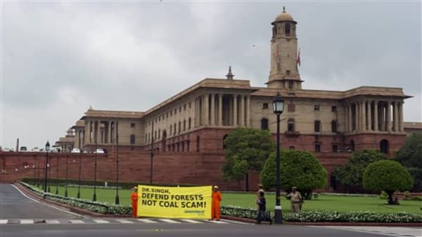Greenpeace activists hold a banner and stand in an area housing the government's seat of power in New Delhi, India, Tuesday, Aug. 21, 2012. Angry opposition lawmakers have shouted and crowded aisles in India's parliament to demand the prime minister resign after a national auditor's report said the government lost huge sums of money by selling coal fields to private companies without competitive bidding. (AP Photo)