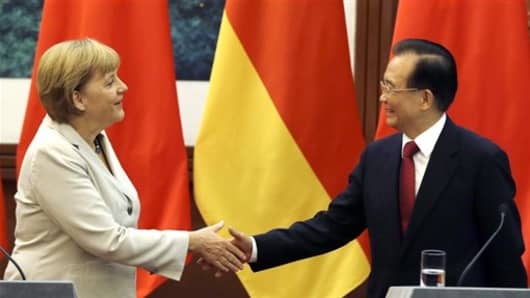 German Chancellor Angela Merkel, left, shakes hands with Chinese Premier Wen Jiabao after a joint press conference at the Great Hall of the People in Beijing Thursday, Aug. 30, 2012. (AP Photo/Ng Han Guan)
