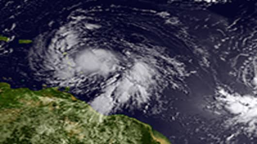 Satellite image provided by National Oceanic and Atmospheric Administration (NOAA), Isaac (L) reached tropical storm status and is approaching the Lesser Antilles islands as it moves westward on August 22, 2012 in the Atlantic Ocean.