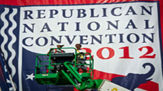 Workers mount a giant banner at the Tampa Bay Times Forum ahead of the Republican National Convention in Tampa, Florida, on August 24, 2012.