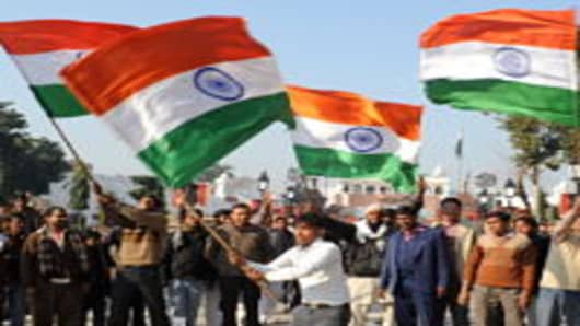 People wave Indian national flags during a ceremony to celebrate India's 63rd Republic Day at the India-Pakistan Wagah border post on January 26, 2012. India celebrated its 63rd Republic Day with a military parade in several towns across the country.
