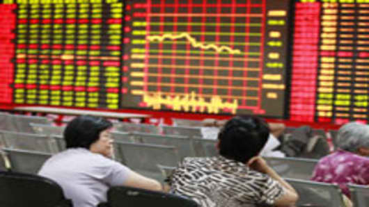 Chinese stock investors monitor their share prices at a stock brokerage firm.