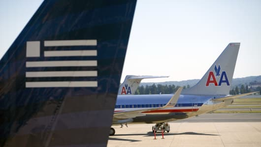 American Airlines and US Airways aircraft sit on the tarmac at Ronald Reagan National Airport in Arlington, Virginia.