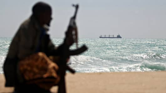 An armed Somali pirate sits along the coastline while the Greek cargo ship, MV Filitsa, is seen anchored just off the shores of Hobyo town in northeastern Somalia where its being held by pirates.