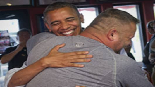 U.S. President Barack Obama hugs Scott Van Duzer, owner of Big Apple Pizza and Pasta Italian Restaurant during a visit to the restaurant in Fort Pierce, Florida.