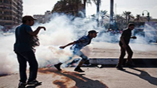 An Egyptian protester runs toward riot police holding a live tear gas canister during clashes near the United States Embassy and Cairo's Tahrir Square on September 13, 2012.