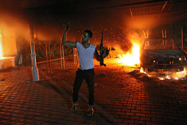An armed man waves his rifle as buildings and cars are engulfed in flames inside the U.S. consulate compound in Benghazi late on Sept. 11, 2012. While Stevens, his aide Sean Smith, and former Navy SEALs Glen A. Doherty and Tyrone S. Woods tried to escape, attackers opened fire – killing all four. Stevens was the first U.S. ambassador killed in the line of duty since Adolph Dubs died in Afghanistan in 1979. Stevens had assisted rebels during their successful uprising against Libyan dictator Moamm