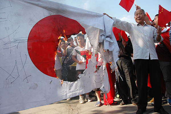 "Japanese flags were set on fire in cities across China as demonstrators showed their anger over Japan ""nationalizing"" the disputed remote islands in the East China Sea."