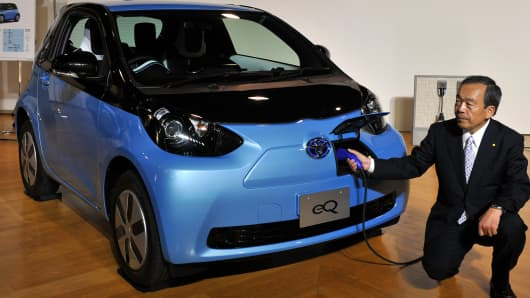 Vice chairman of Toyota Motor, Takeshi Uchiyamada (R), introduces the company's new compact electric vehicle called the 'eQ', at the company's showroom in Tokyo on September 24, 2012.