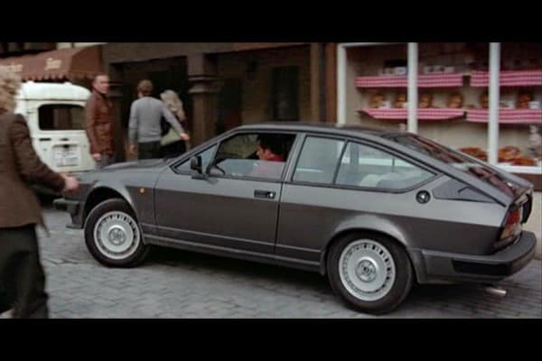 In the 1983 film Octopussy, James Bond (played by Roger Moore) steals an Alfa Romeo GTV6 as he heads towards Octopussy's circus troupe on a U.S. air force base in West Germany. In the scene, Bond is pursued by two police BMWs and a motorcycle through German highways and side streets, roaring the iconic Alfa Romeo engine