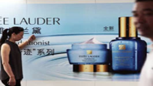 People walk in front of an Estee Lauder advertisement at a metro station in Shanghai, China.
