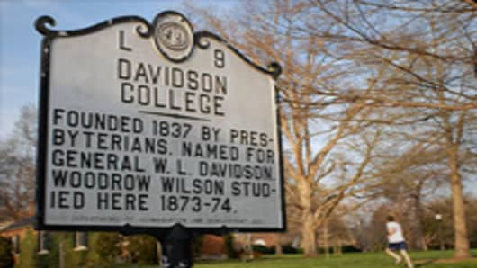 A runner passes a sign on the campus of Davidson College in Davidson, North Carolina.