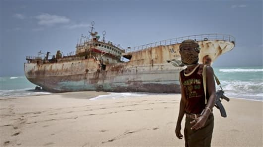 In this photo taken Sunday, Sept. 23, 2012, masked Somali pirate Abdi Ali stands near a Taiwanese fishing vessel that washed up on shore after the pirates were paid a ransom and released the crew,.