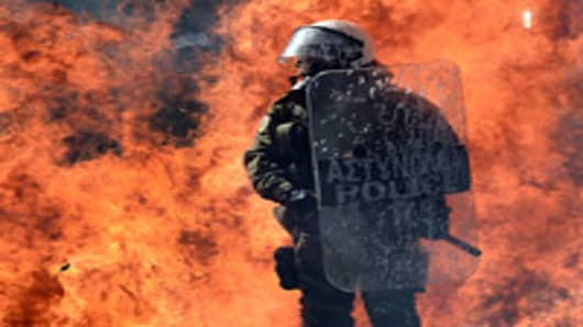 A fire bomb explodes behind a riot police squad on September 26, 2012 in Athens during clashes with demonstrators at a 24-hours general strike. Police in Athens clashed with hooded youths throwing firebombs on the sidelines of a large demonstration against a new round of austerity cuts.