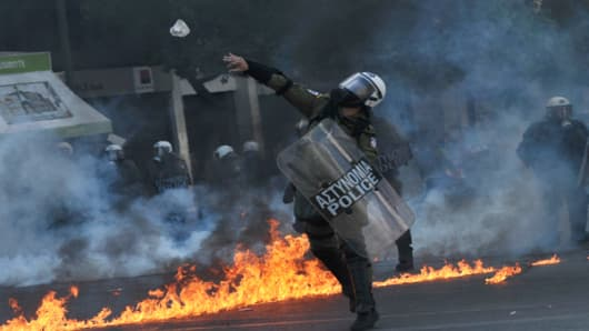 A police officer throws a stone toward demonstrators on September 26, 2012 during a 24-hours general strike in Athens. Police let of tear gas and used batons to disperse protestors.