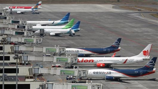 In this Tuesday, Sept. 25, 2012 photo, budget airlines' passenger jets, Malaysia's AirAsia, top, Indonesia's Badavia Air, third from bottom and bottom, and Indonesia's Lion Air, second bottom, are parked on the tarmac with Indonesian planes of domestic airline Merpati Nusantara, second top, and the flagship carrier Garuda Indonesia at Juanda International Airport in Surabaya, East Java, Indonesia. From almost none a decade ago, Asia now has more than 50 low cost carriers.