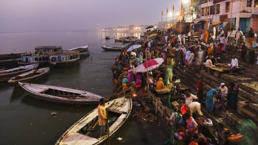 Crowd by harbor in Uttar Pradesh, India at dawn