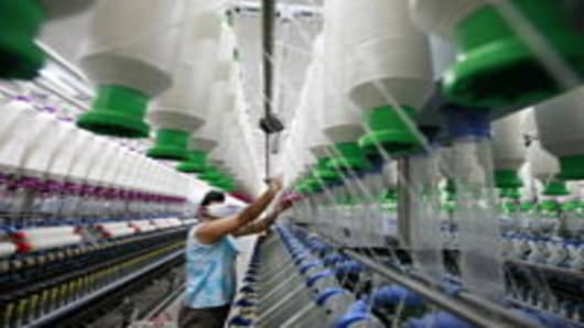 A worker operates machines for making yarn at a textile factory in Huaibei, east China's Anhui province.