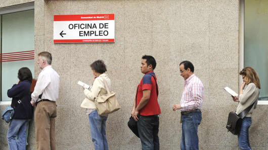 People wait in line at a government employment office in the center of Madrid, Spain.