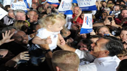 US Republican presidential candidate Mitt Romney holds a child during a campaign rally at the Wings Over the Rockies Air and Space Museum in Denver, Colorado, on October 1, 2012.