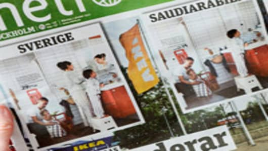 A person holds in Stockholm the October 1, 2012 issue of the free daily Metro newspaper, featuring two versions of the same photo from Swedish furniture giant Ikea's yearly catalog -- the Swedish catalog (L) and the Saudi (R) one.