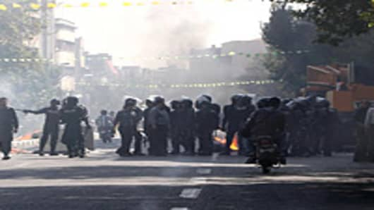 Iranian riot police stand next to a garbage container which is set on fire by protesters in central Tehran, near the main bazaar, on October 3, 2012, in the first sign of public unrest over Iran's plunging currency. The rial, lost more than half of its value since last week as the plunge has greatly increased inflation in Iran, which is widely seen as far higher than the official 23.5 percent given by the central bank.