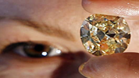 A model displays a natural yellow 42.02 carat diamond at a public auction show in Mumbai. India.