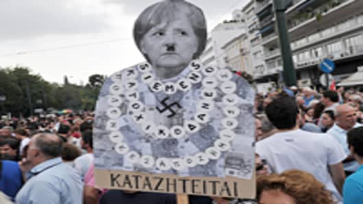 A protester holds a plackard of German Chancellor Angela Merkel featuring a Hitler moustache near the Greek parliament in Athens during a demonstration against the vist of the German Chancellor Angela Merkel on October 9, 2012.
