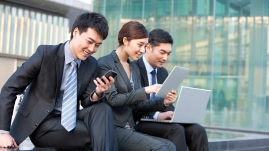 Asian business people using smartphone and laptops
