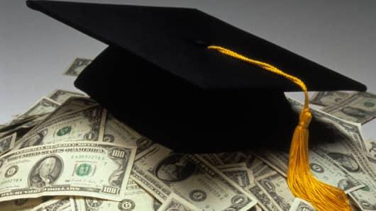 college graduation cap on pile of money